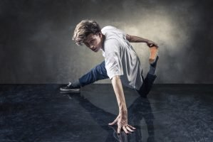 Footworks Dance Studio - urban hip hop dancer over grunge concrete wall