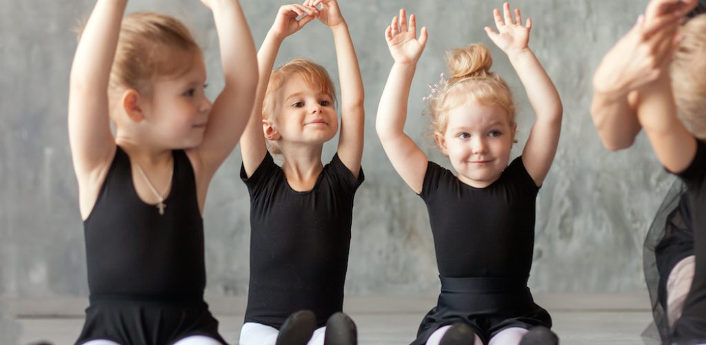 Little girl ballerinas in black dresses sitting on the floor and hold hands over their head for warm-up in a dance studio